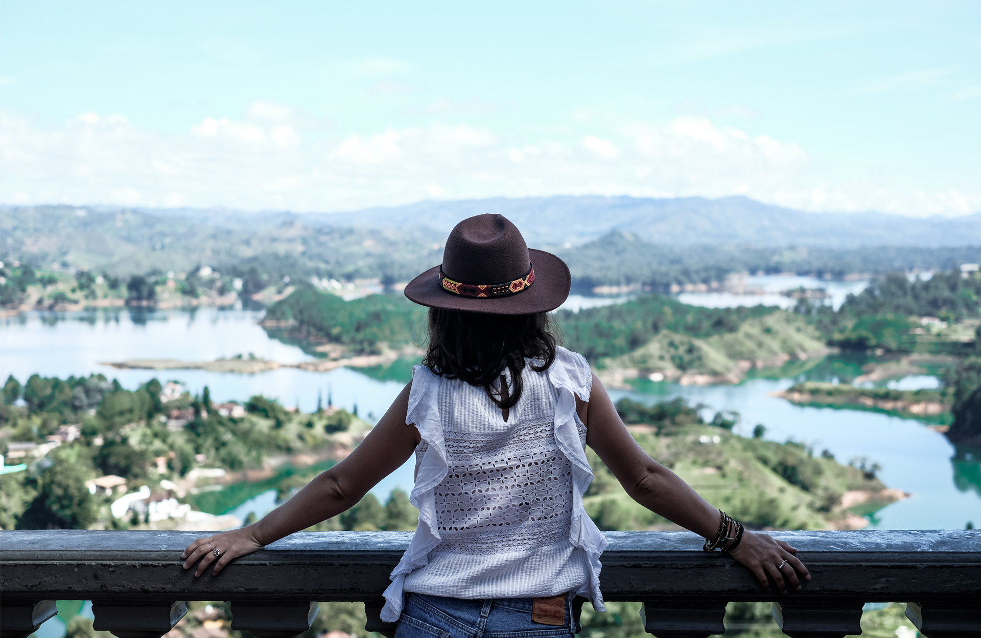 back of a girl with hat looking at the guatape water reservoir