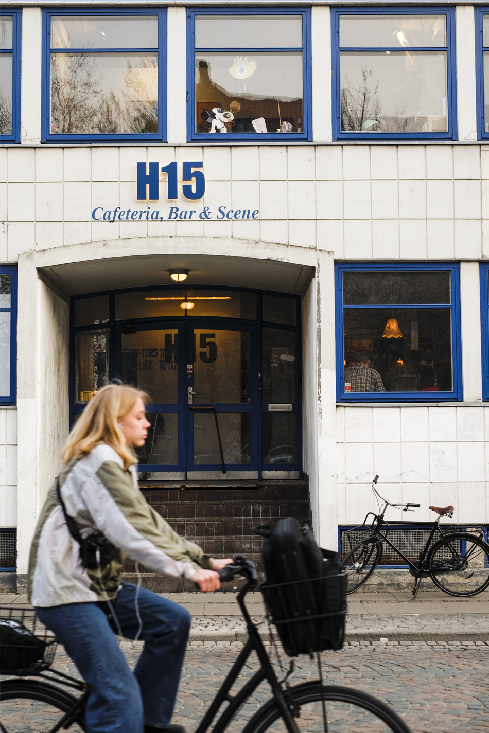 woman biking front of a white and blue building