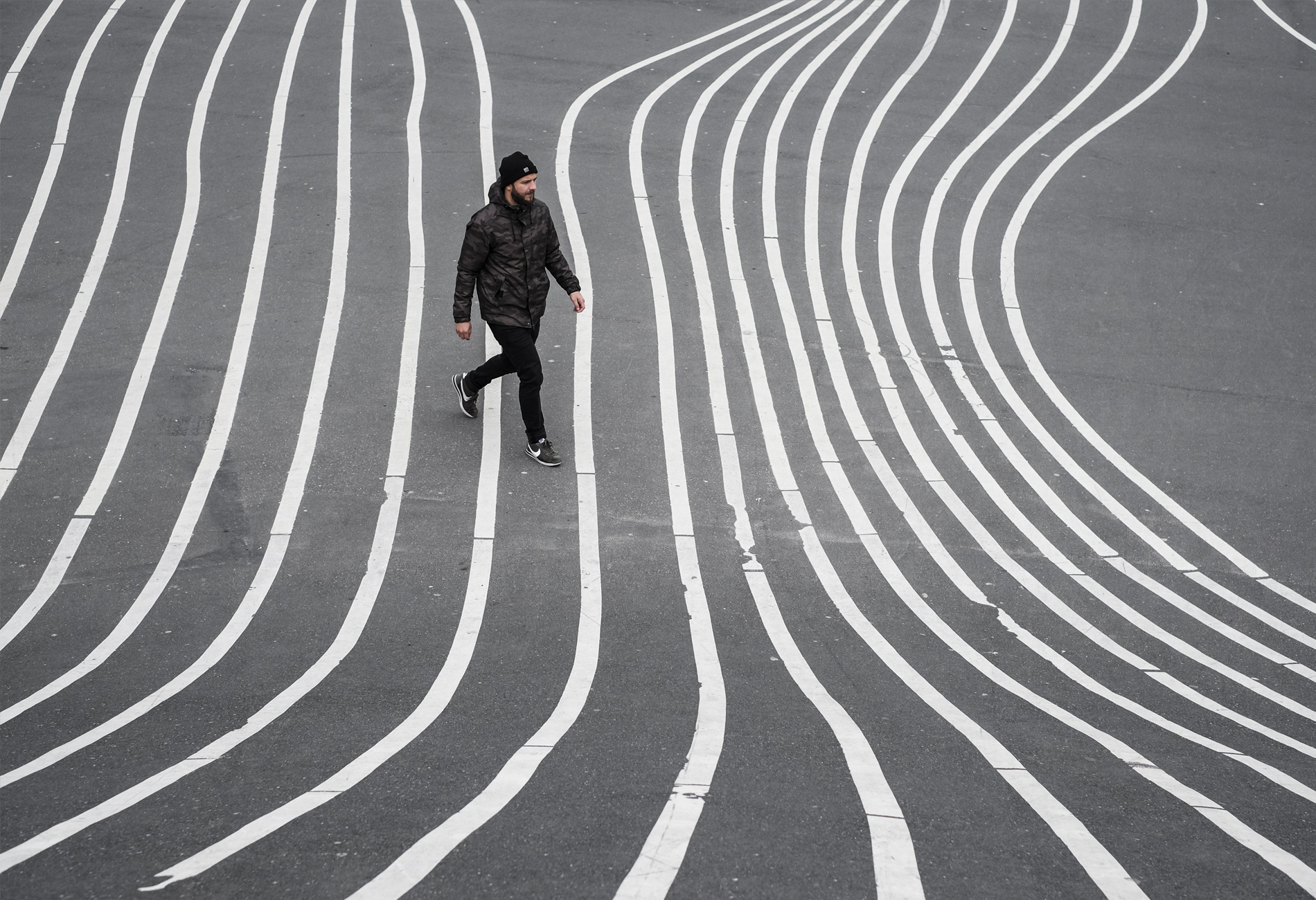 man walking at the middle of the lines of superkilen