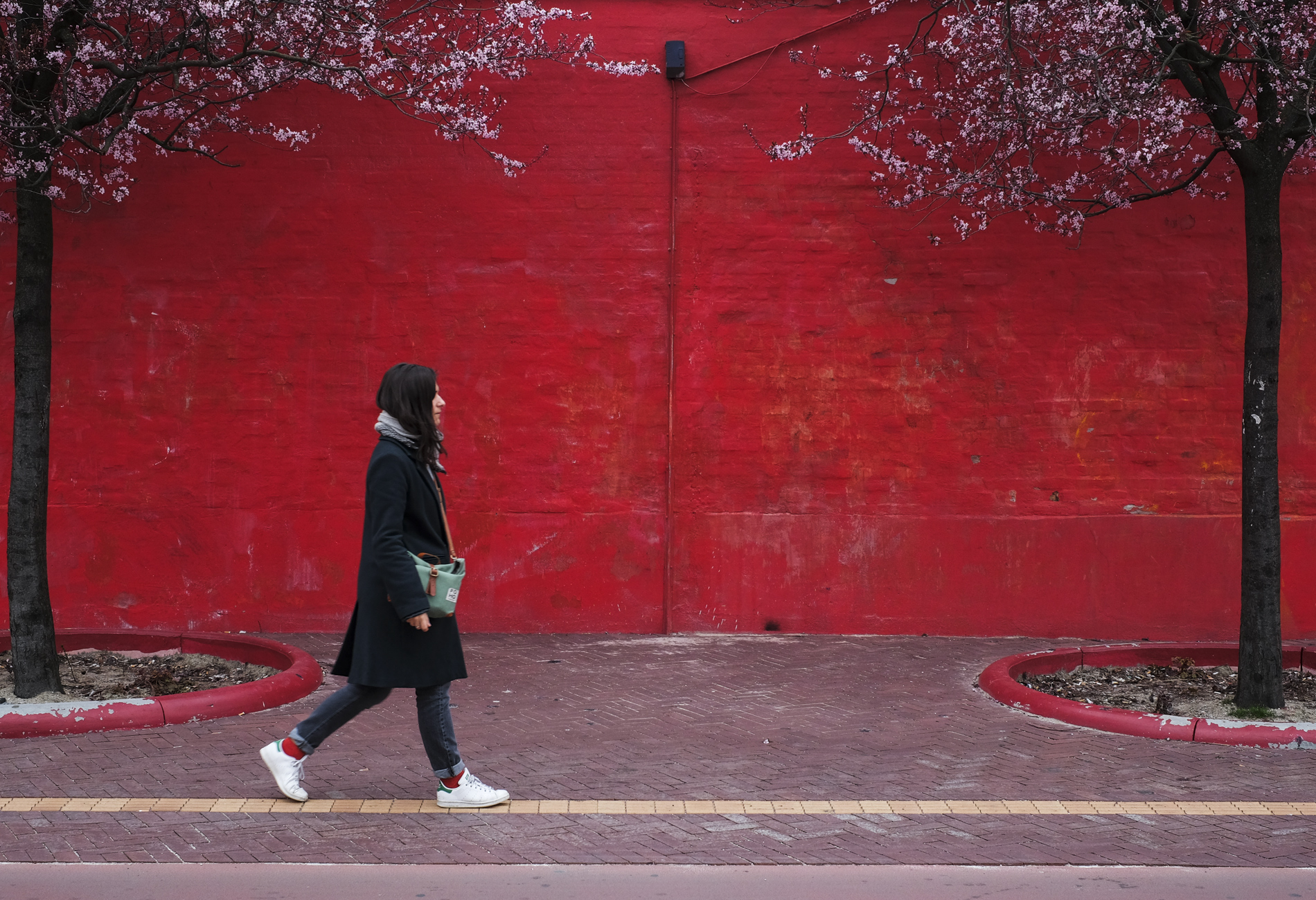 woman walking front of a red wall