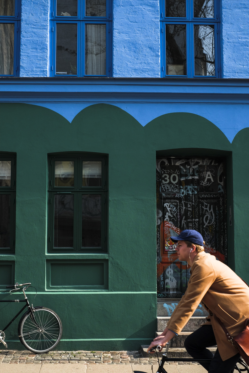 Guy driving a bike, with a cap, infront of a blue and green building in Copenhagen
