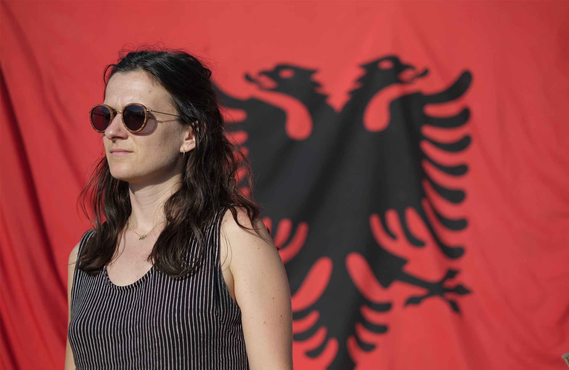girl in front of Albanian flag road trip in Albania