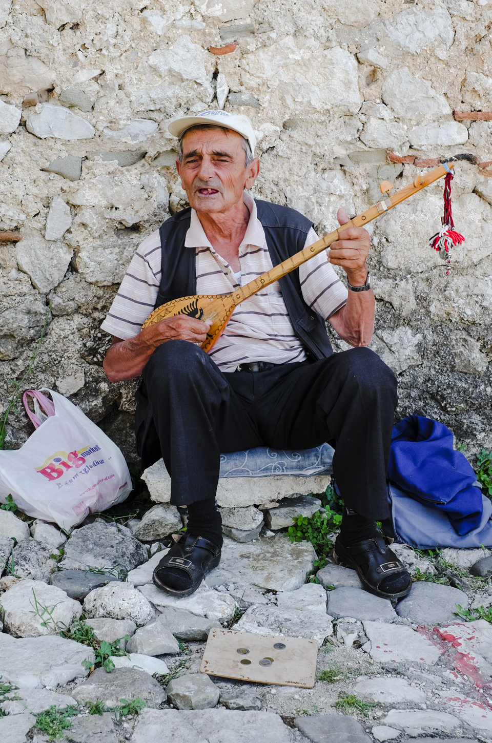 Old man sitting down playing the guitar during road trip in Albania