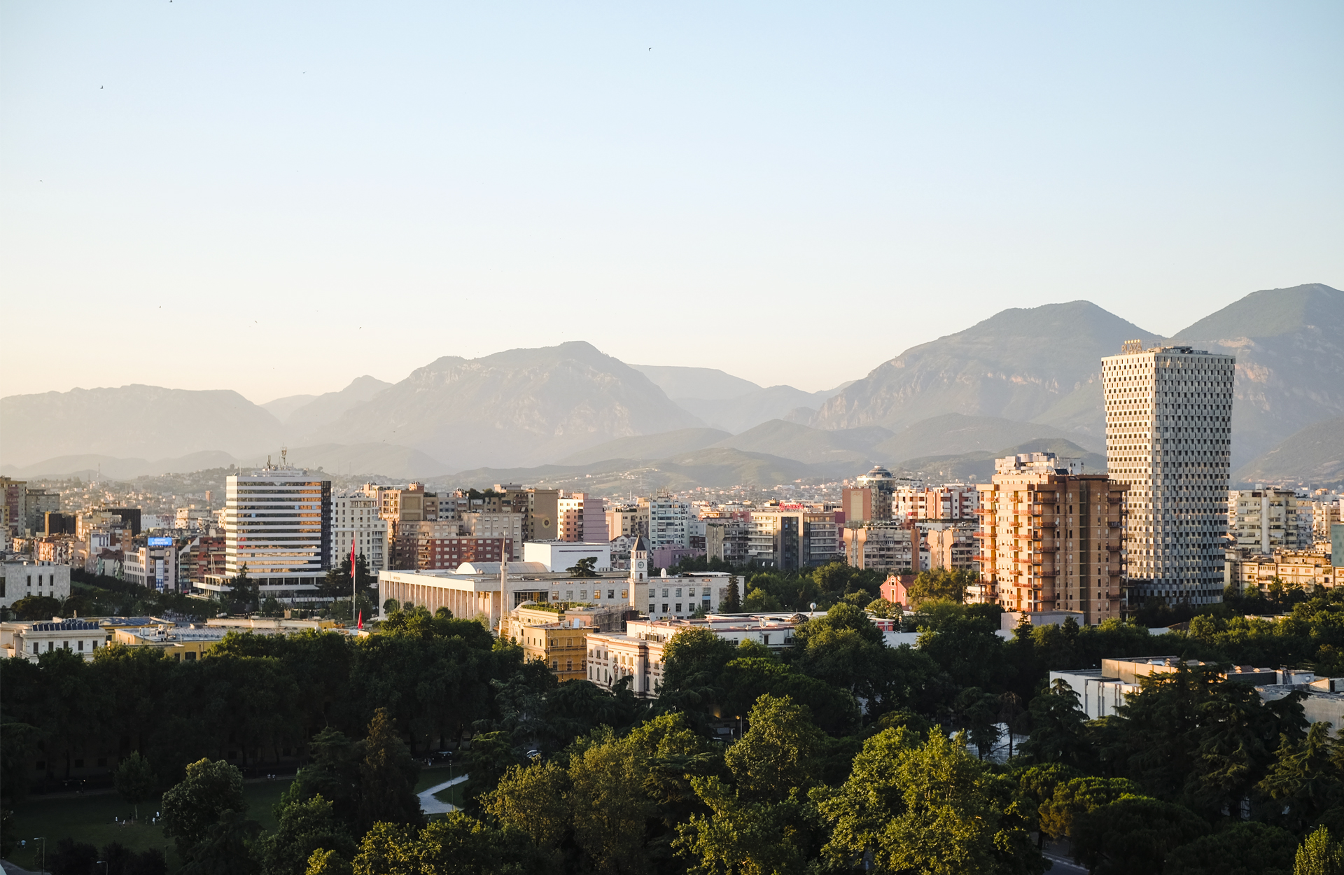 Tirana's skyline from a roof top with mountains in the back.