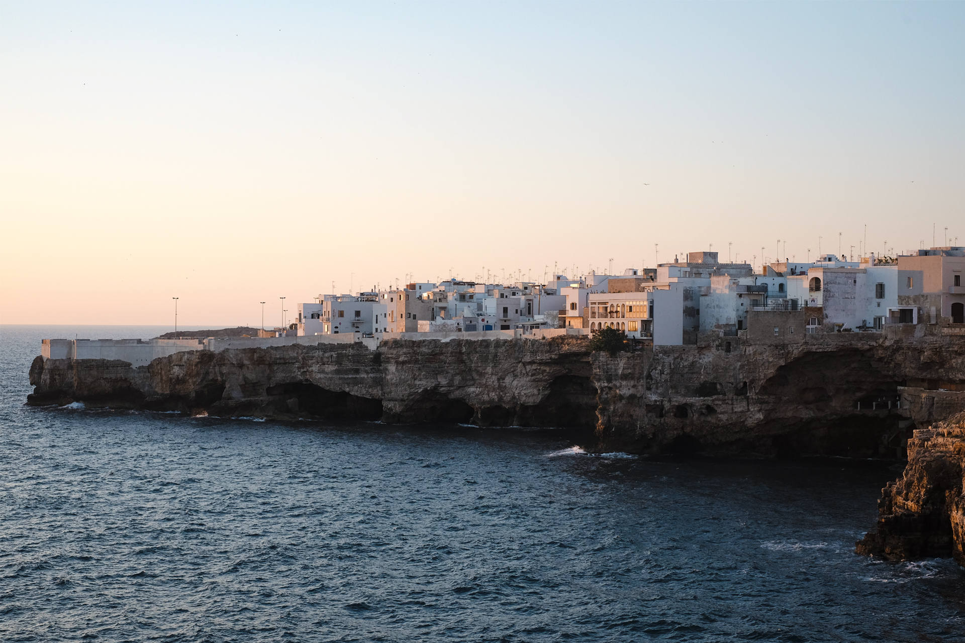 glimpse of the Cliffs and town of Polignano a Mare in the light of the sunrise