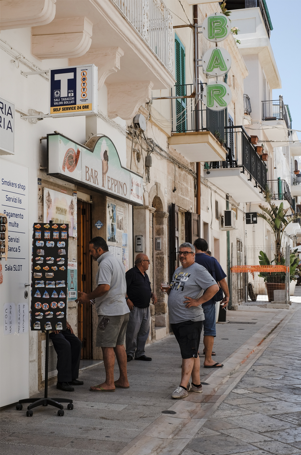 A glimpse of Puglia man standing and talking outside a bar