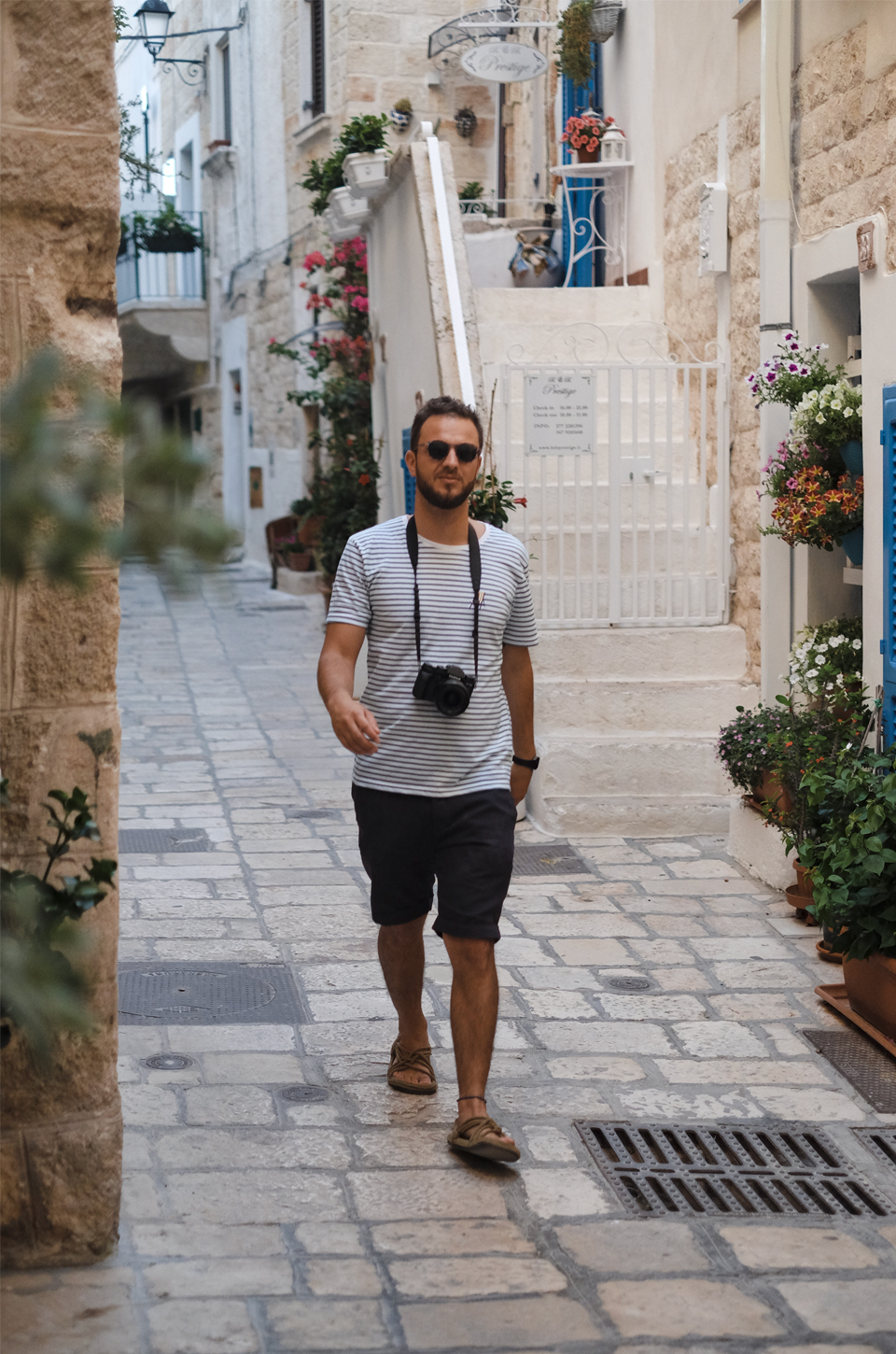 A glimpse of Puglia, a man with a camera and sunglasses so sunglasess walking in the streets of Polignano