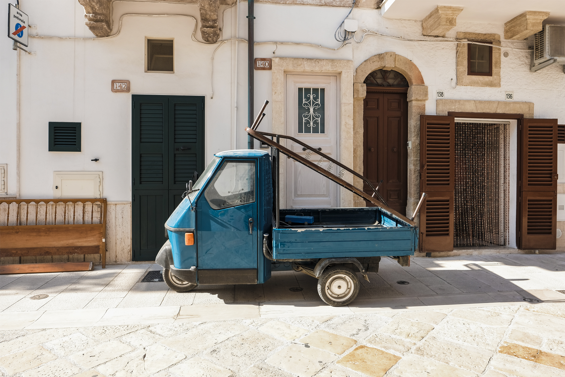 Blue tuck tuck parked in front of white building a glimpse of Puglia