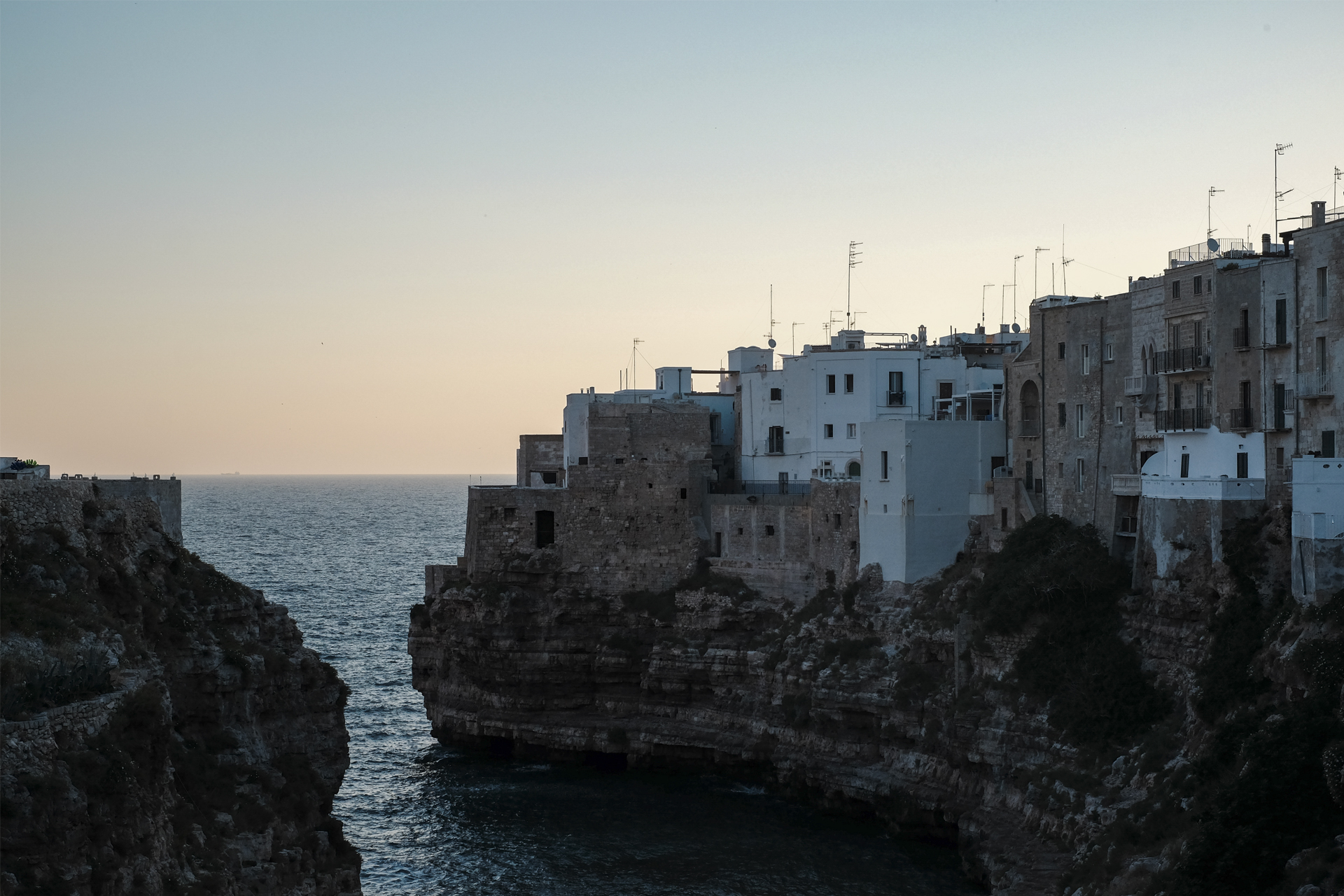 view of Lama Monachile or Cala Porto at sunrise in Polignano