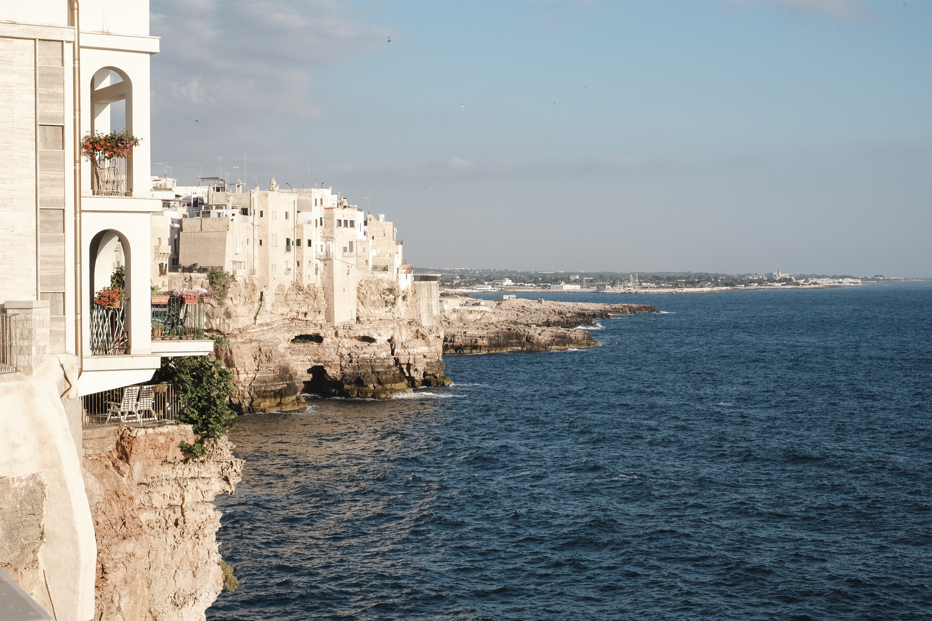 View of the sea, cliffs and buildings from a balcony in Polignano