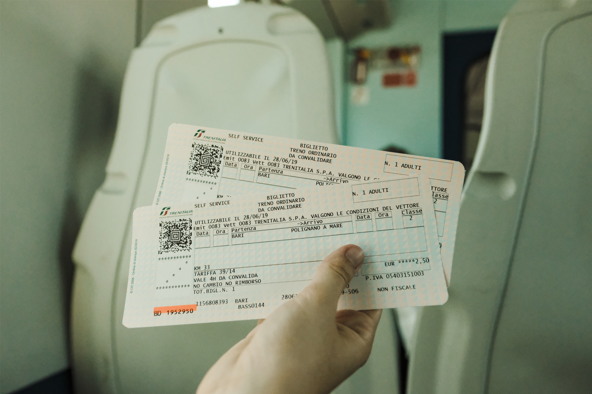 Hand holding train tickets in Bari