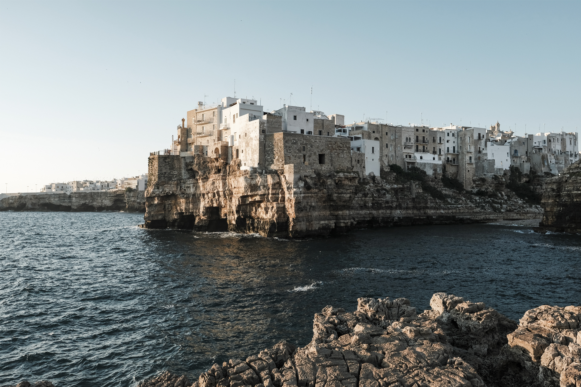 View of the city over the cliffs and the blue sea of Polignano a Mare