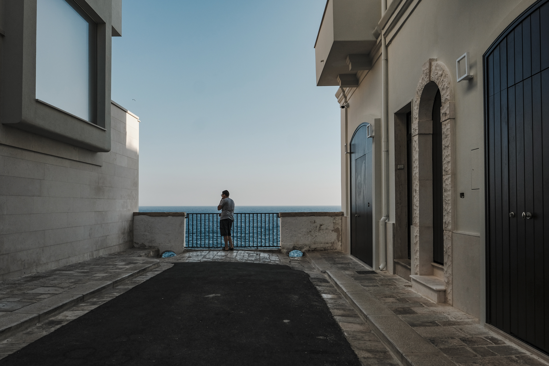 Man with shorts in a balcony looking at the blue sea in Polignano a Mare