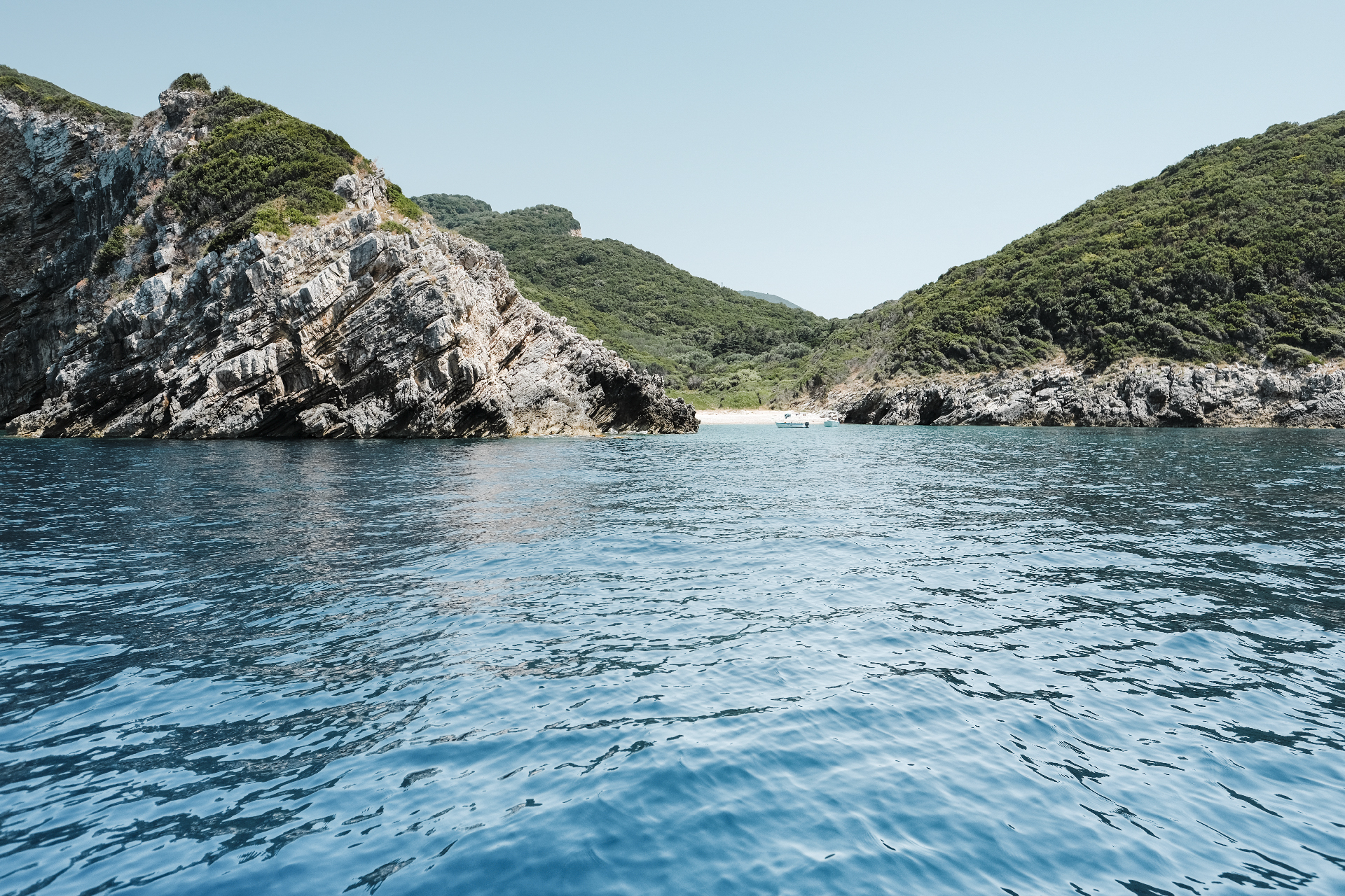 Cliffs and beach of the Adriatic sea seen from a boat, things to do in Corfu