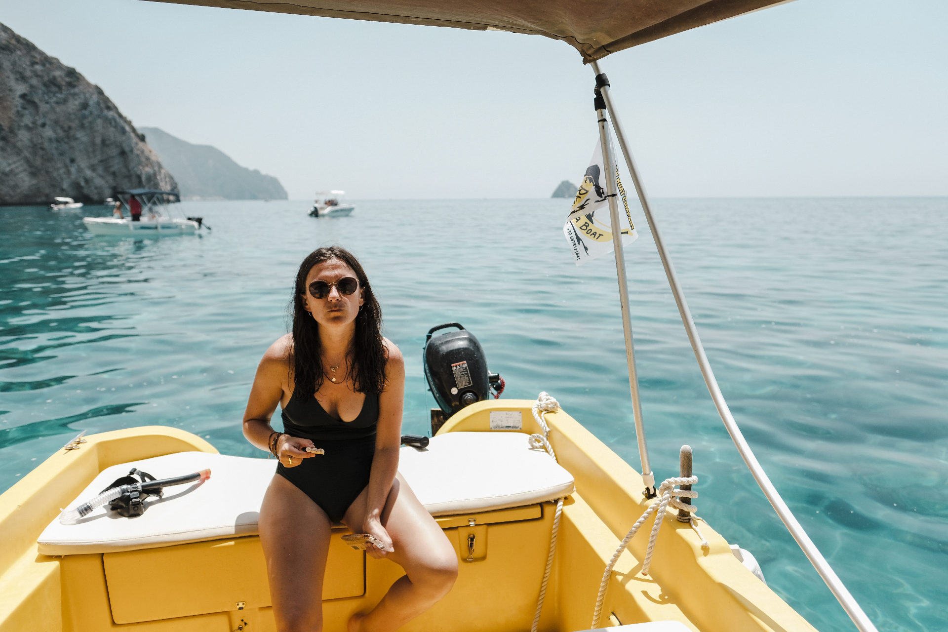 Girl sitting on a yellow boat, weekend in Greece