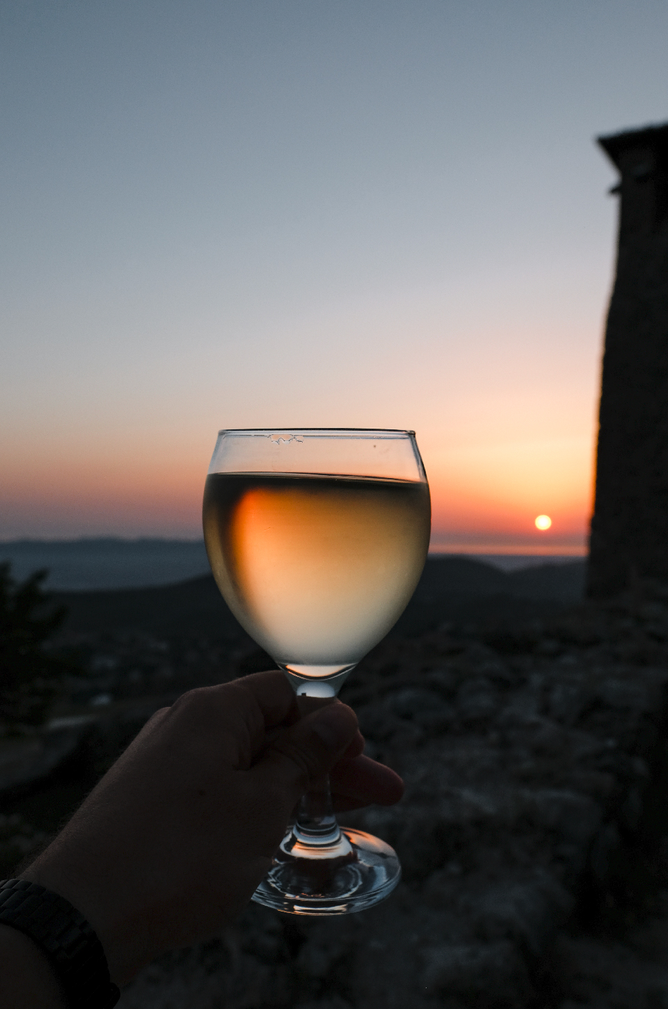 Glass of white wine infront of the sun at sunset
