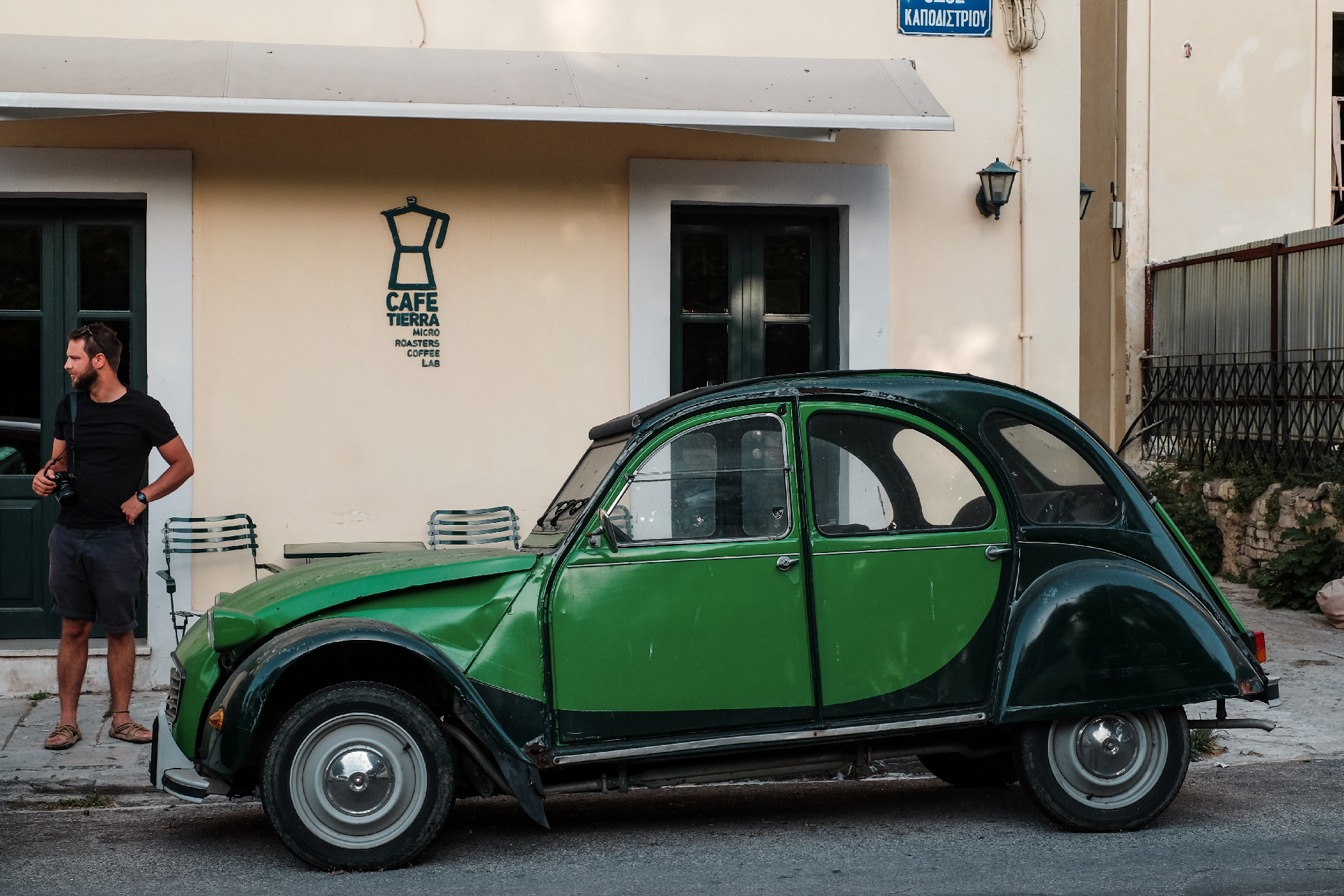 Man beside a green car outside Tierra cafe, weekend in Greece