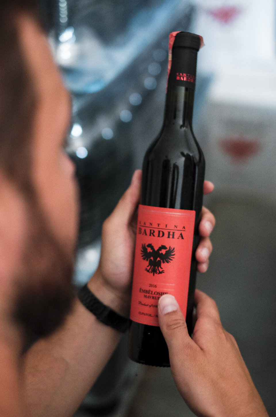 Man holding a bottle of wine from bardha winery