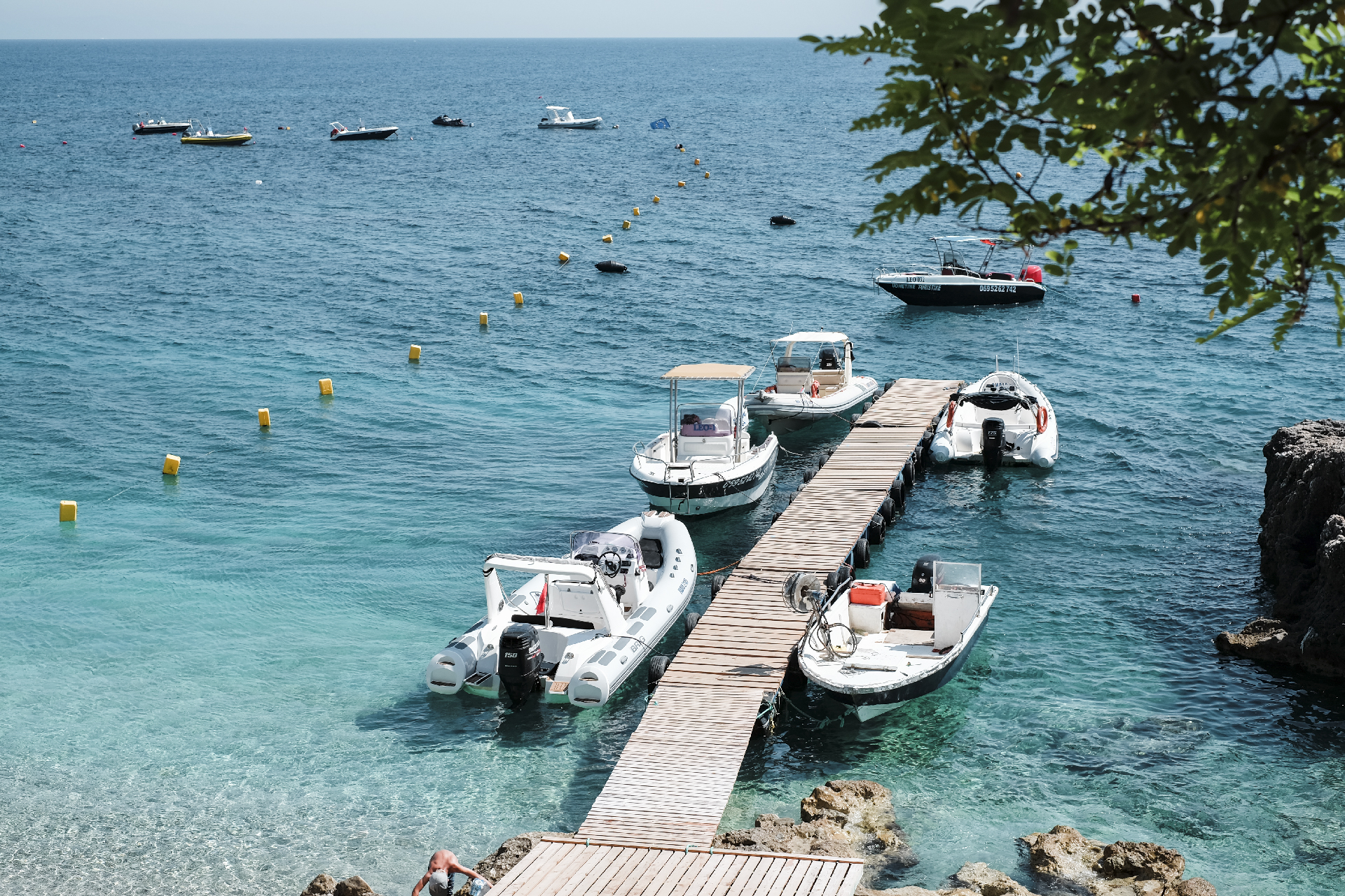 Wooden Pier with small boats in Dhermi beach, Albania road trip