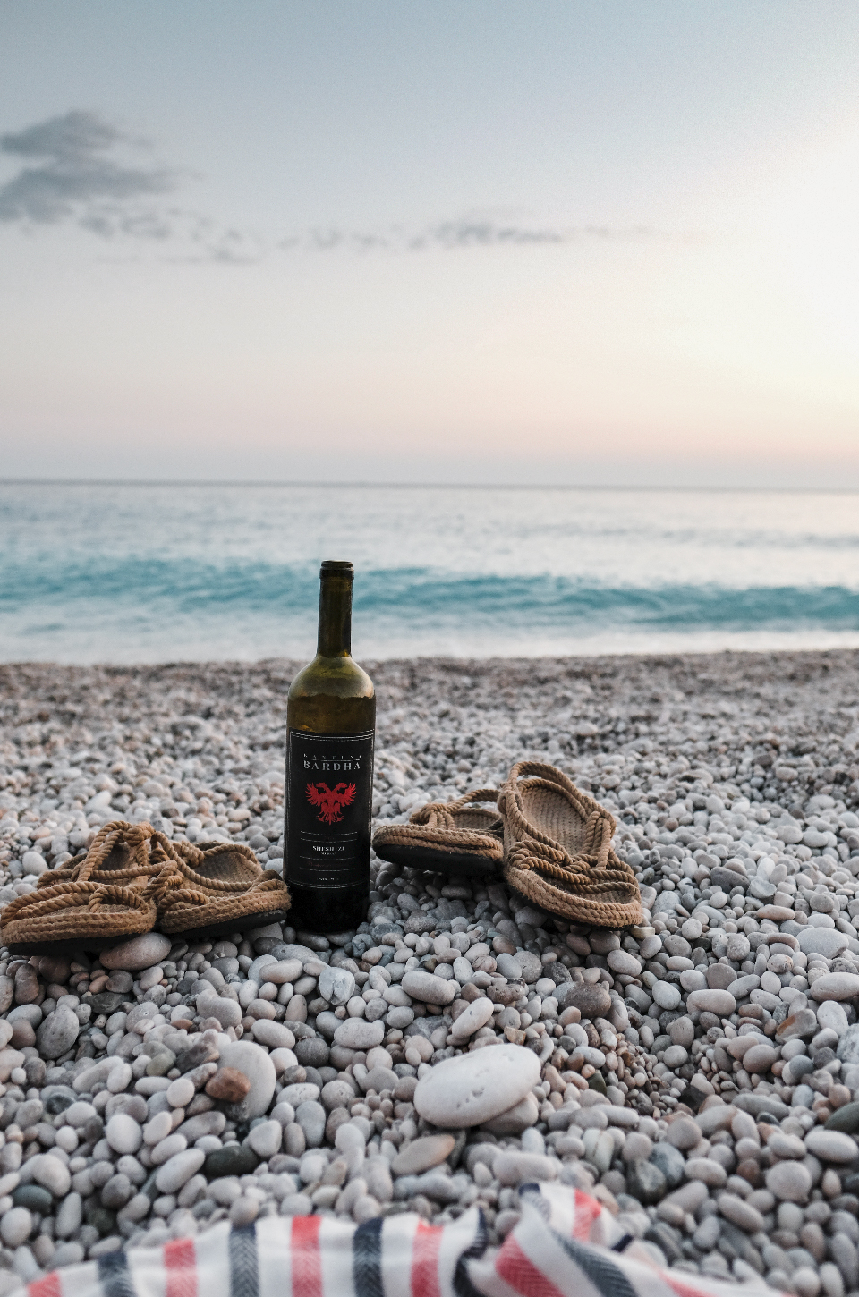Bottle of wine and sandals infront of the ocean, best beaches in the Riviera, Albania