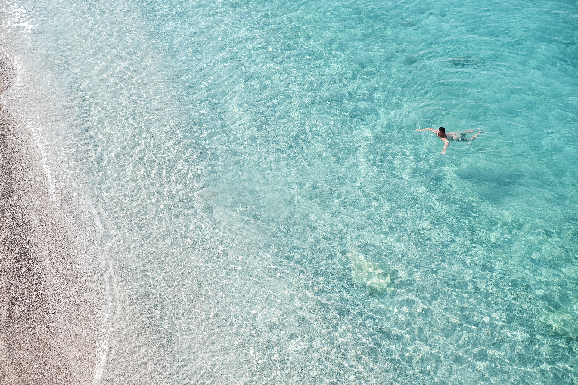 Man swimming in crystaline water, best beaches in the Riviera Albania