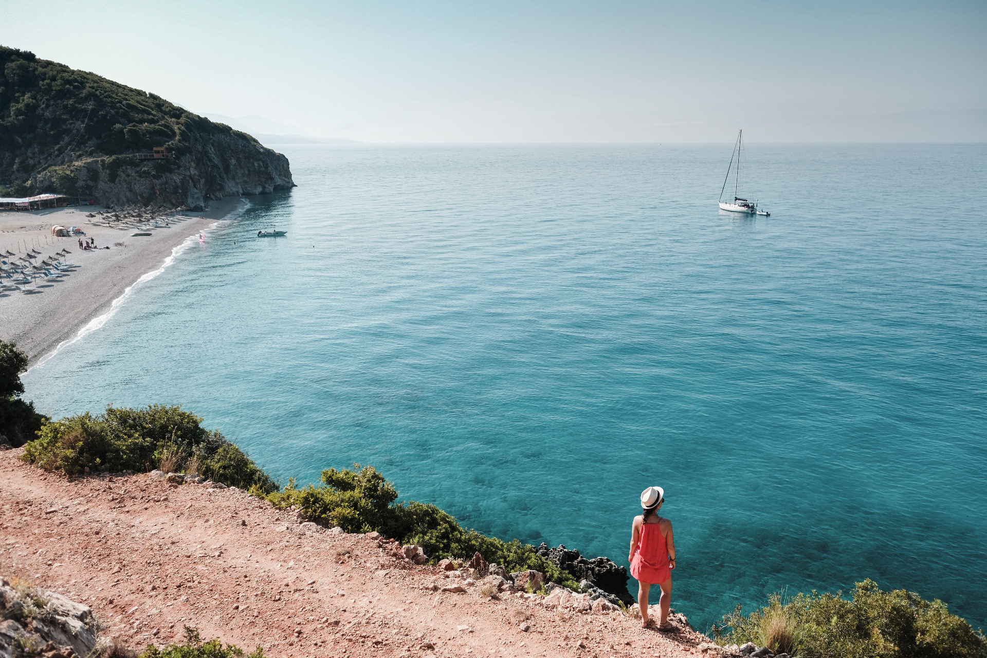 girl with a hat wearing pink looking at a boat in Albania, best beaches in the Riviera