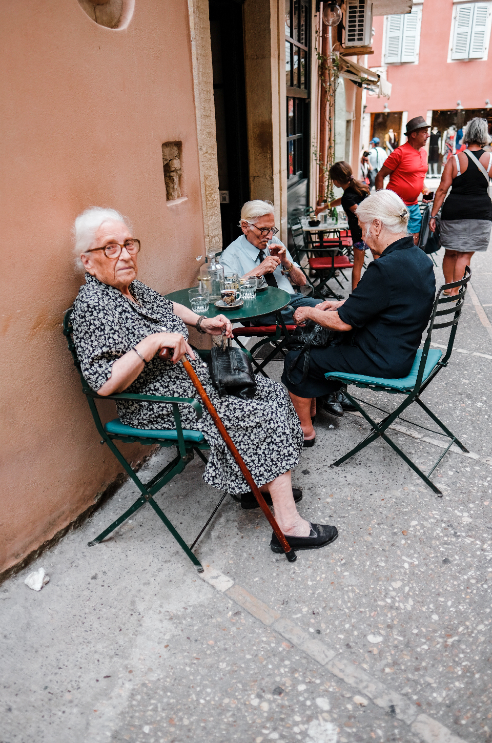 Group of old people siting around a table drinking coffee in Corfu's old town. A weekend in Greece