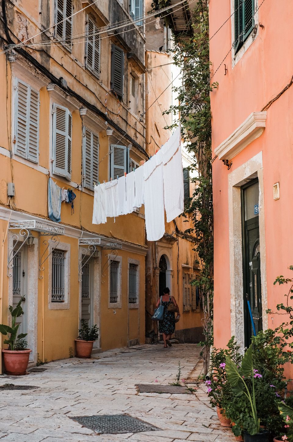 Woman walking through an Alley under White hanging clothes