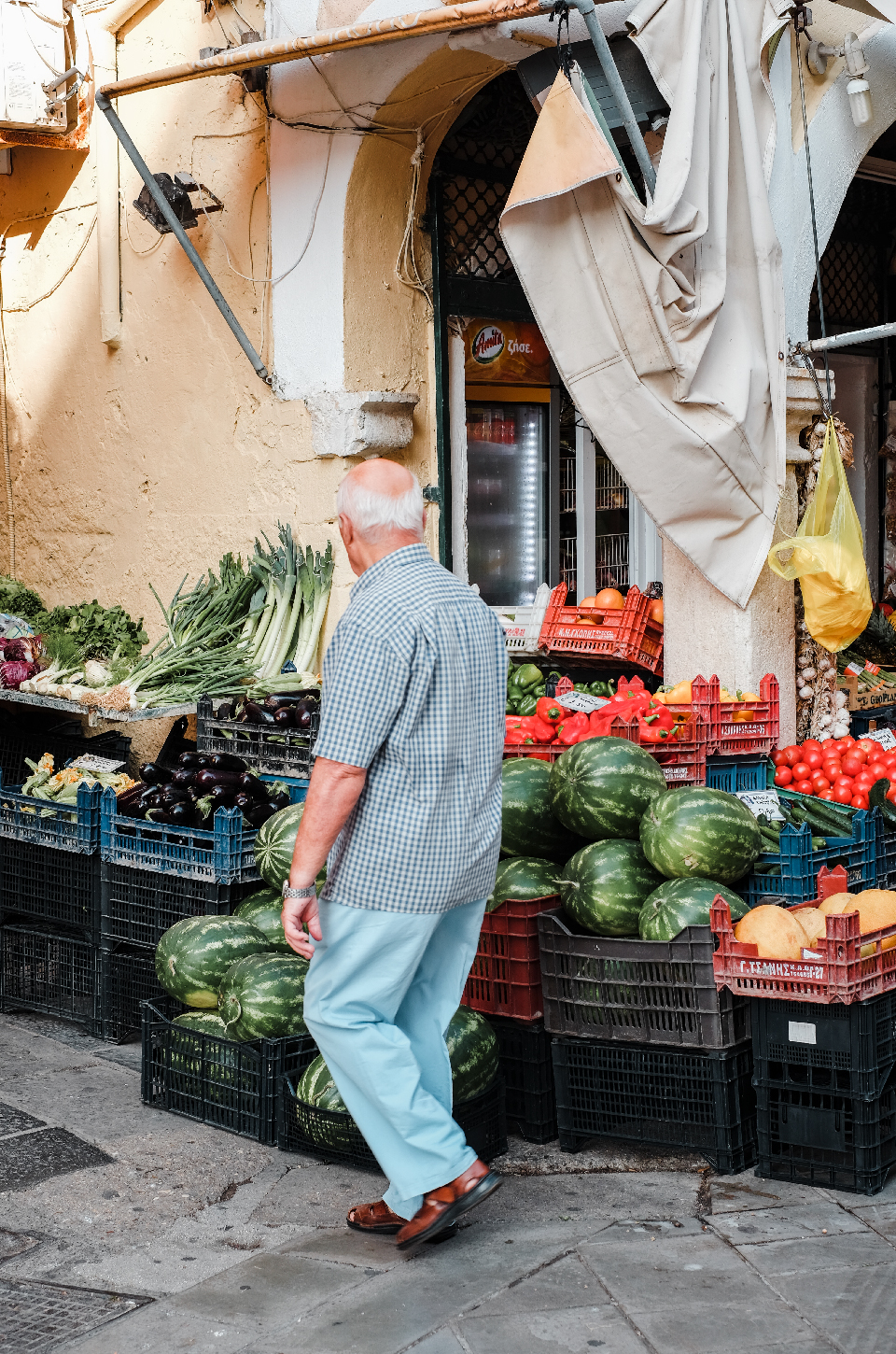 Old man walking infront of a fruit stand in Corfu's old town, weekend in Greece