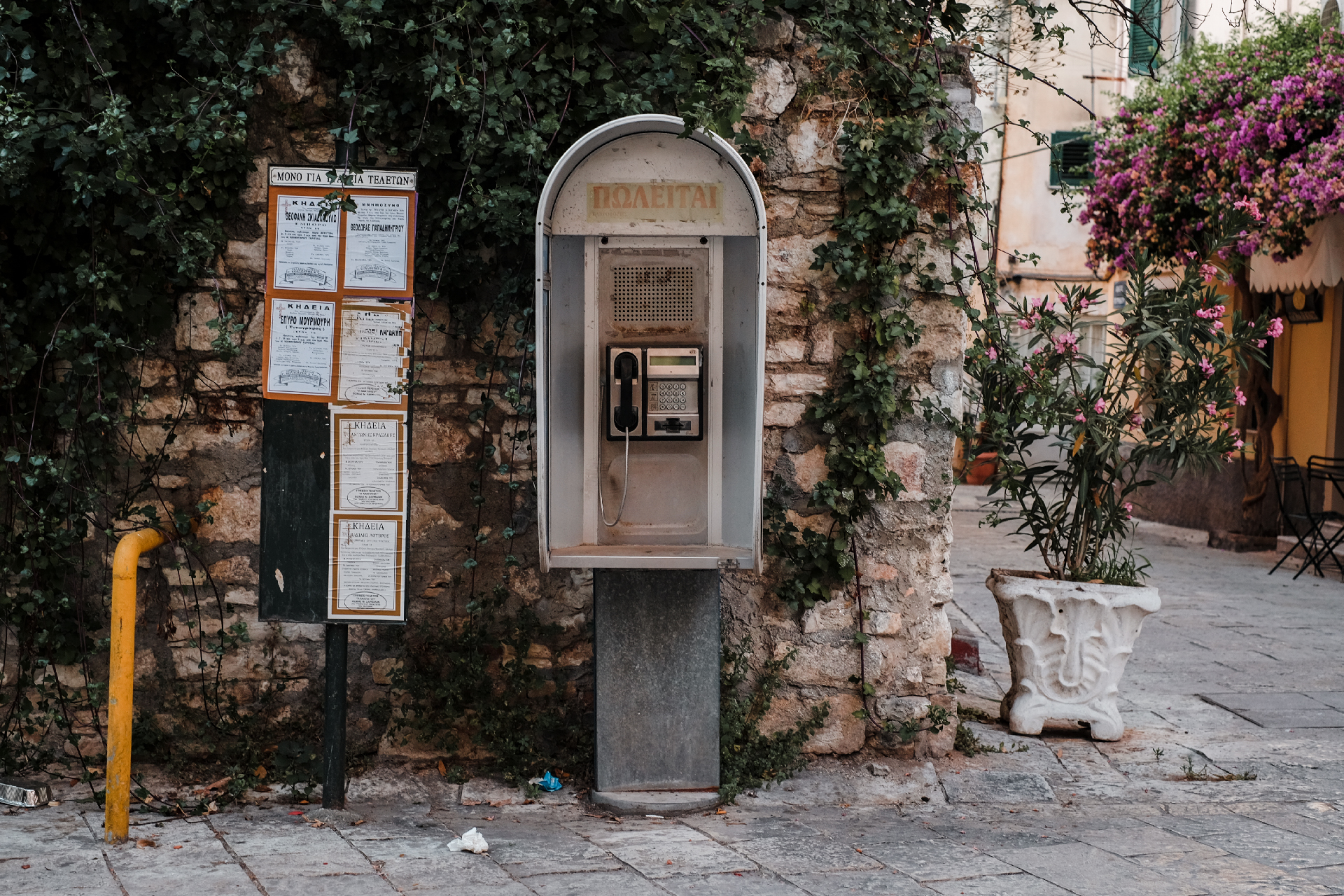 Pay telephone against a rock wall, what to do in Corfu.