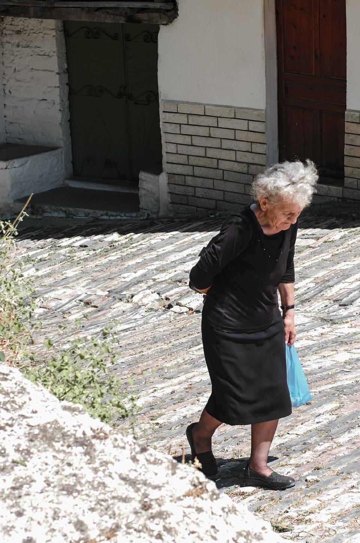 Old woman dressed in black walking up the street in Gjirokastër