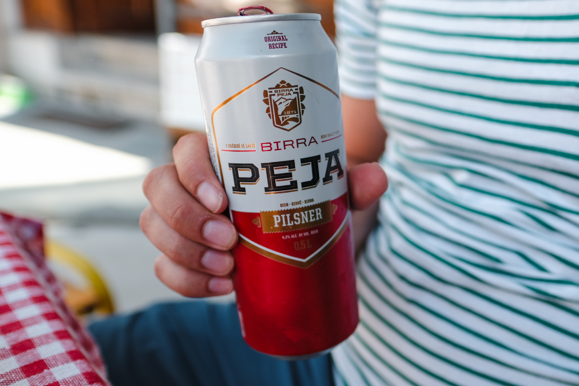 hand holding a can of beer birra peja, the center of Albania