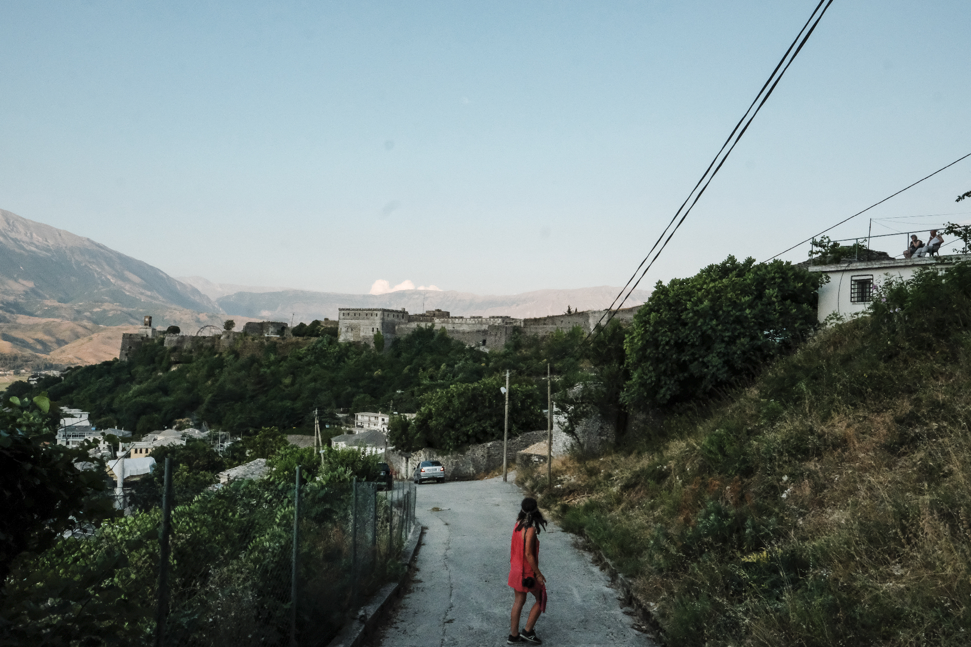 girl walking down the streetso of Gjirokastër looking at the castle
