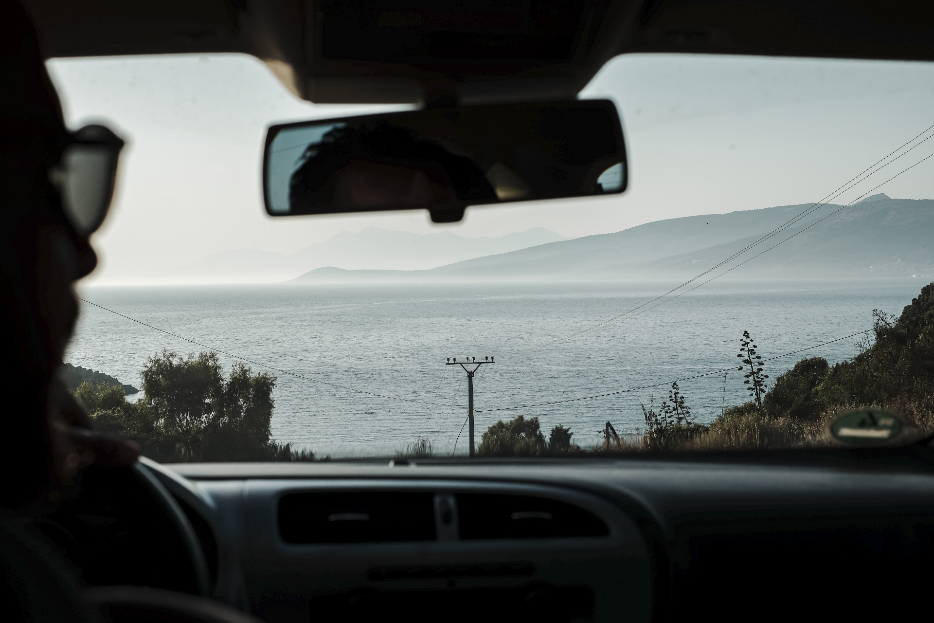 man driving a car with a view on a beach of the riviera and mountains, road trip