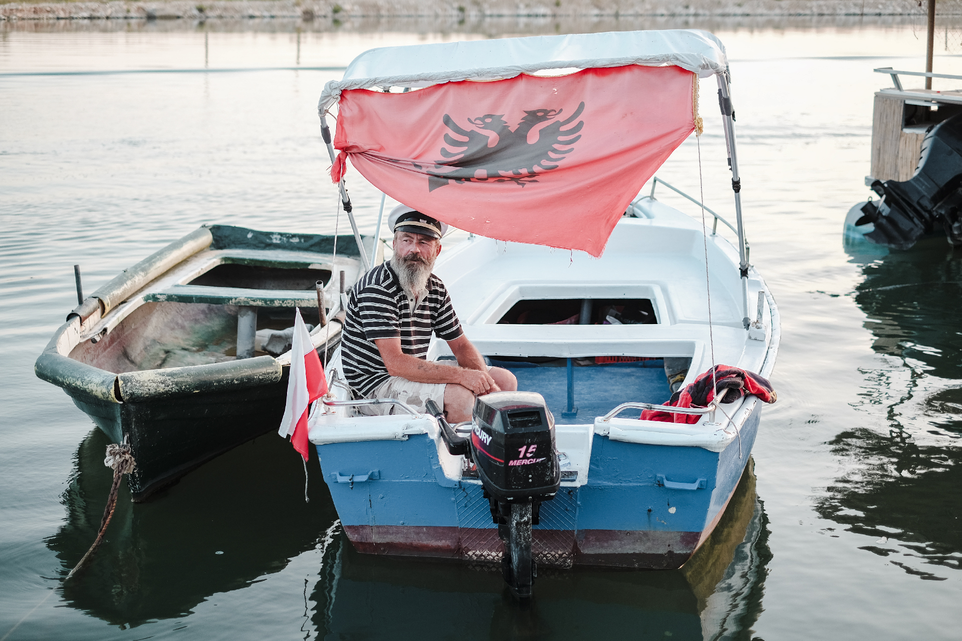 Capitan on his boat with the flag of Albania, road trip best beaches